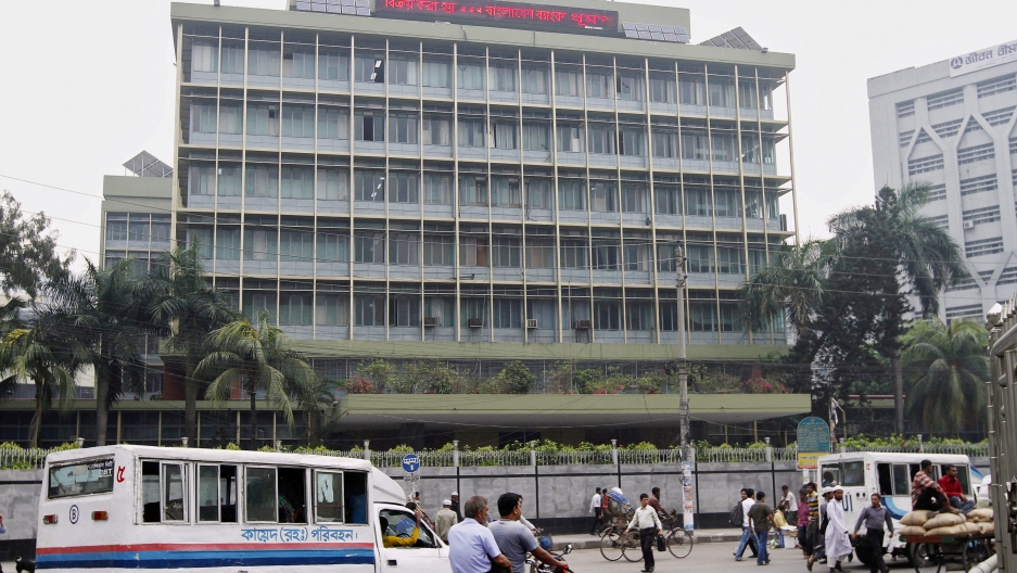 Commuters pass by the front of the Bangladesh central bank building in Dhaka, Bangladesh, on March 8, 2016.