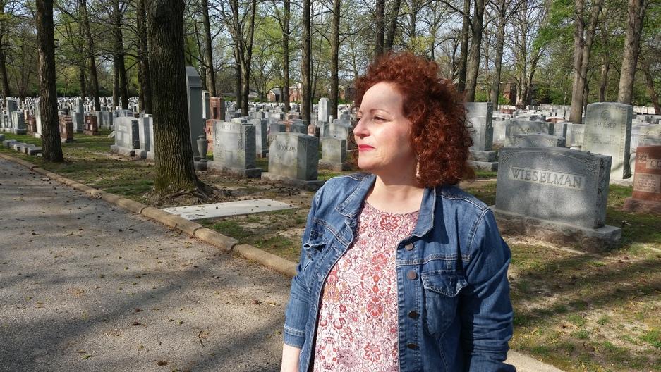 Karen Aroesty standing in front of the headstones of Chesed Shel Emeth cemetery