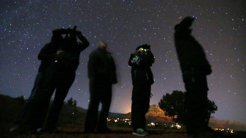 People use night vision goggles to look at the night sky during an Unidentified Flying Object (UFO) tour in the desert outside Sedona, Arizona, Feb. 14, 2013.