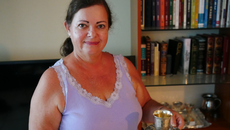 Mely Revai in San Juan, Puerto Rico, holding a ritual kiddush cup she brought from her home Caracas.