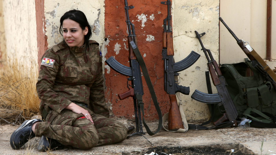 A Yazidi woman who joined the Kurdish Peshmerga forces sits next to rifles in the town of Bashiqa, after it was recaptured from the Islamic State, east of Mosul, Iraq Nov. 10, 2016.