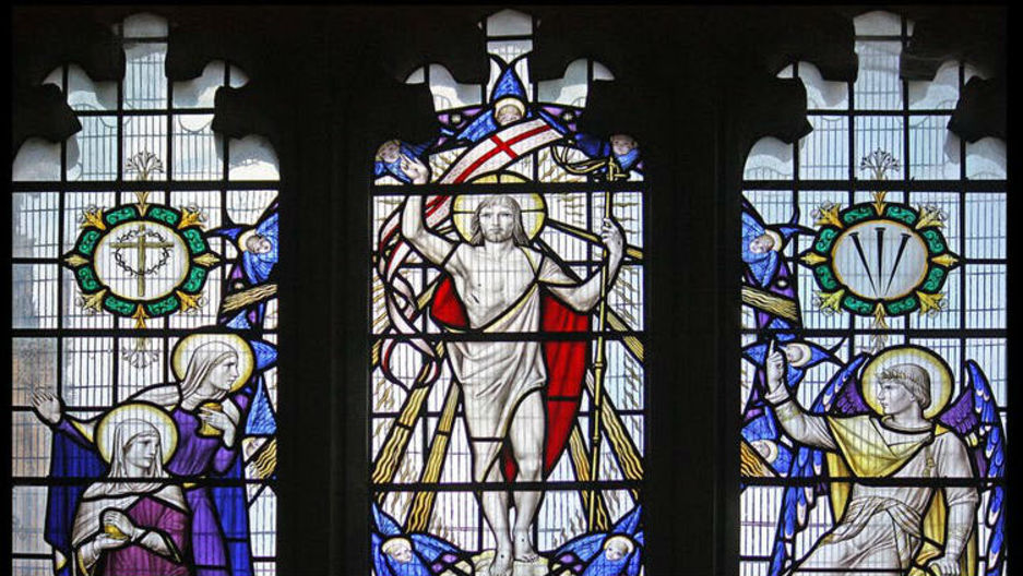 Colorful stained-glass windows depicting the resurrection of Jesus Christ at Sherborne Abbey in Dorset, England.