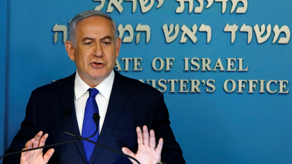 Israeli Prime Minister Benjamin Netanyahu speaks at a lectern before a blue background during a news conference at the Prime Minister's office in Jerusalem on April 2, 2018.