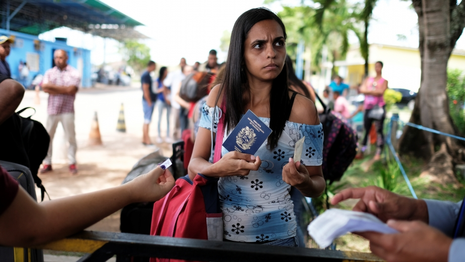 A Venezuelan woman shows her passport and identity card at the Pacaraima border control, Roraima state, Brazil, November 16, 2017.