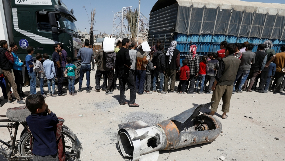 A boy stands next to the remains of a missile as people line up for aid in the city of Douma in Damascus, Syria, on April 16, 2018.
