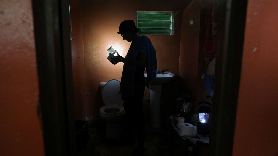A woman uses a solar lamp inside the darkened bathroom of her home in Naguabo, Puerto Rico, on January 27, 2018.