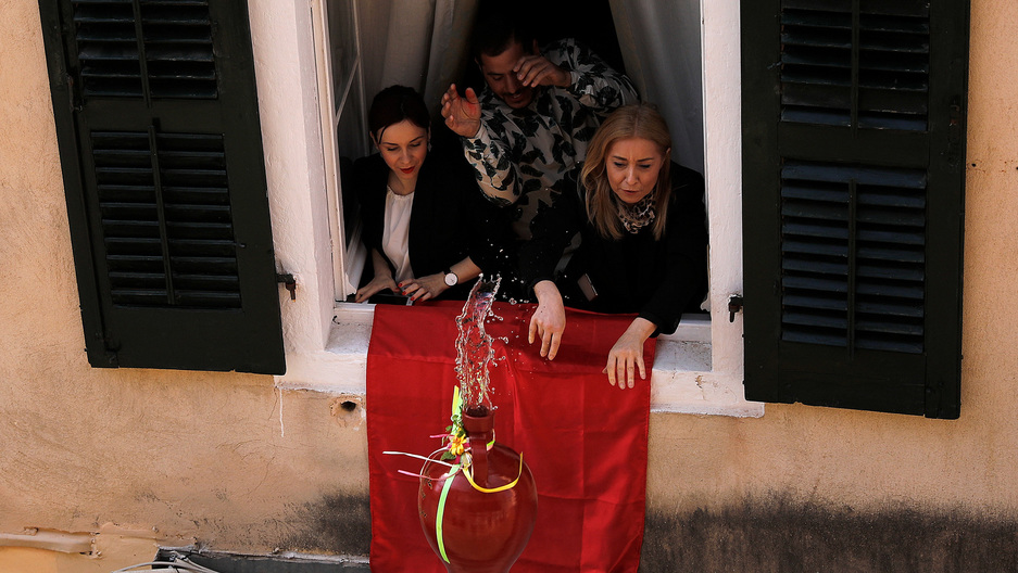 Three people at a window are dropping a bright red jug down onto the street below. Water has fallen out the top and the pot falls to the ground.