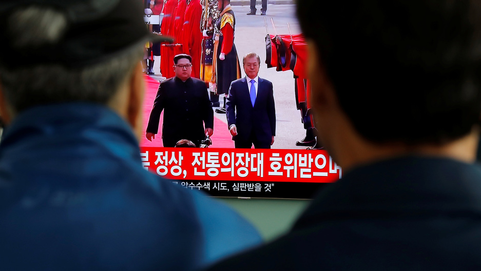 Two men with dark hair stand and watch a television screen with Korean characters showing the inter-Korean summit.