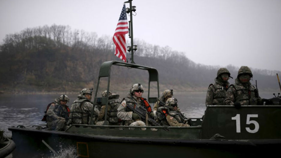 US army soldiers ride in a boat topped with an American flag while taking part in a US-South Korea joint river-crossing exercise near the demilitarized zone separating the two Koreas in Yeoncheon, South Korea, on April 8, 2016.
