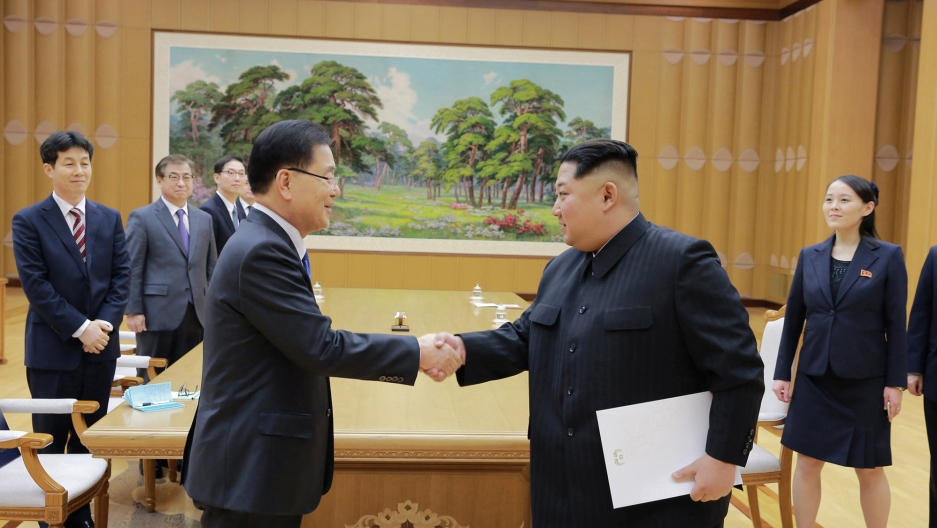 North Korean leader Kim Jong-un on the right shakes hands with a member of the special delegation of South Korea's President in a boardroom.