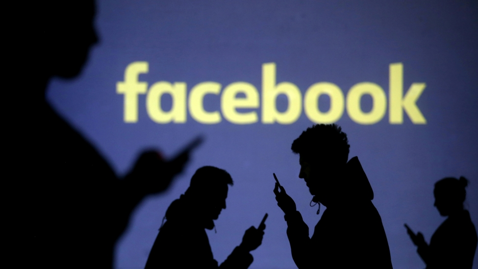 Silhouettes of people looking at their mobile phones in front of Facebook's logo.