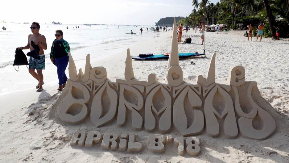 A sand sculpture reads Boracay April 8, 2018, as tourists wander by.