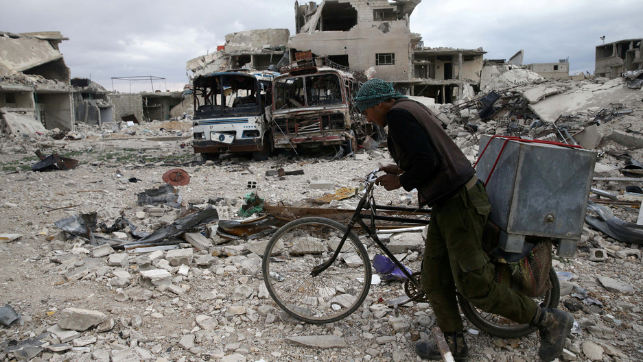 A man walks with his bicycle passed bombed buildings and two burned out busses.