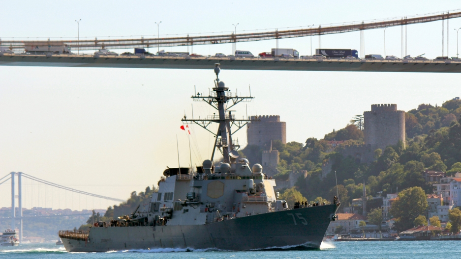 USS Donald Cook sails in the Bosphorus strait in Istanbul with a long cable bridge in the background.
