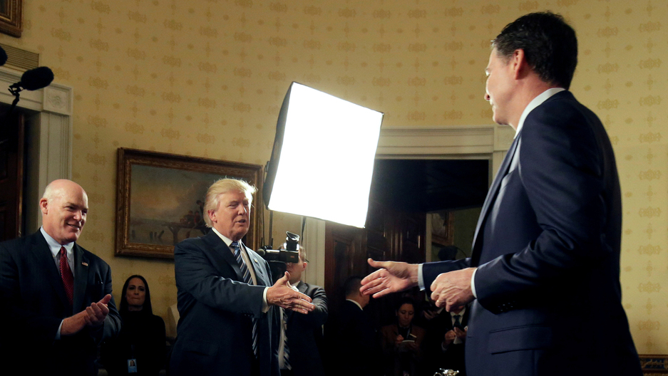 President Donald Trump greets Director of the FBI James Comey as Director of the Secret Service Joseph Clancy (L), watches at the White House.