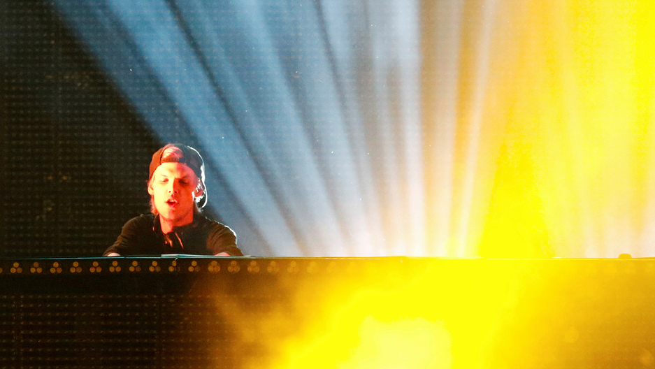 DJ Avicii performs while bright lights shine behind him during a concert at Brooklyn's Barclay's Center in New York.