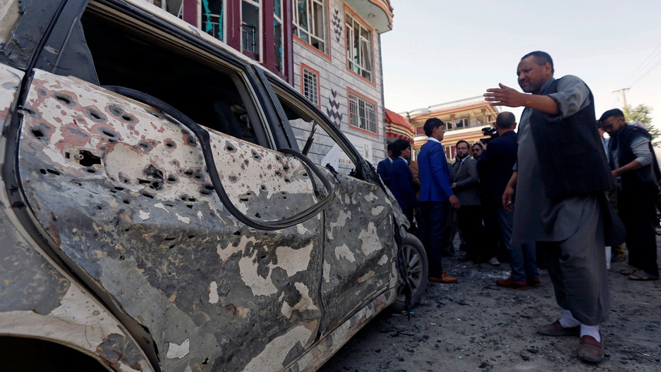 A man points left to a car that shows the impact of a bomb blast in Kabul.
