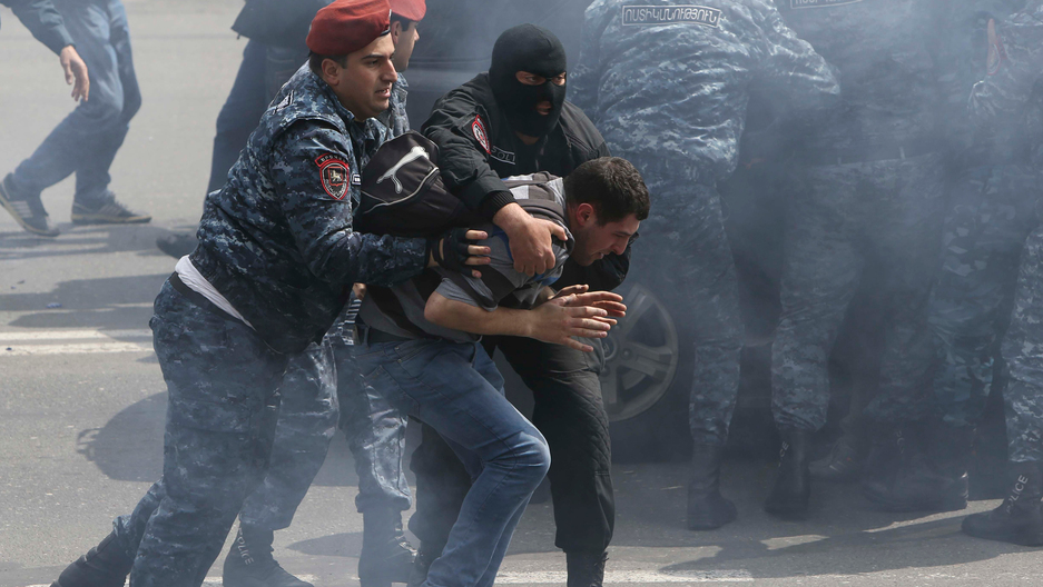 Red beret-wearing Armenian law enforcement officers detain a man during a protest.