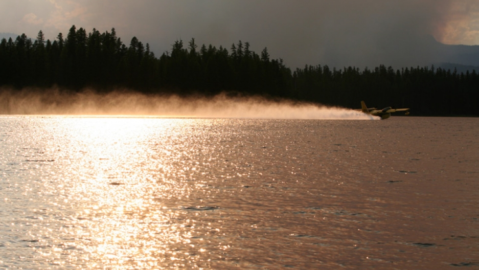 A firefighting plane skims the surface of a lake in Montana