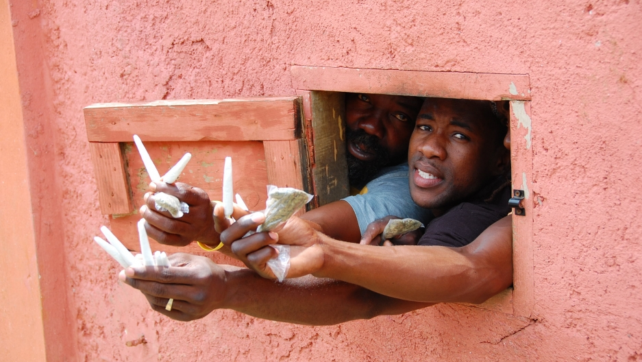 Men hold up marijuana at the house of reggae legend Bob Marley.