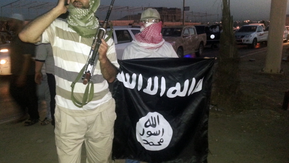 """A fighter of the Islamic State of Iraq and the Levant (ISIL) holds a weapon while another holds a flag in the city of Mosul, shortly after the Islamic State captured the city. The flag reads, """"There is no God but God, and Muhammad is the Messenger of God."""
