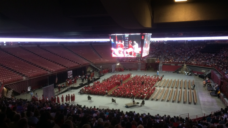 A big screen above a high school graduation ceremony in a stadium