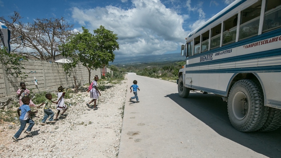 Migrant children board a bus outside the Notre Dame de Lourdes School in Anse-a-Pitres, Haiti, to return to their shelters after morning classes.