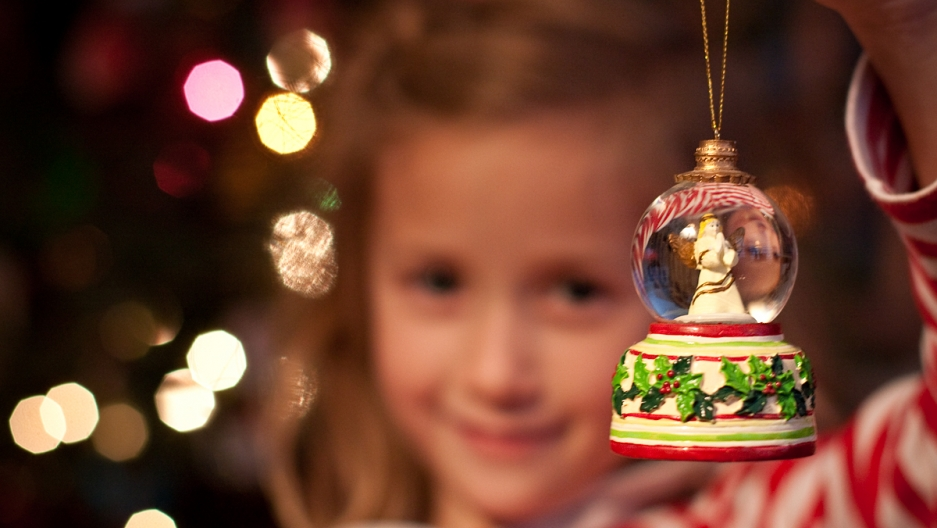 A girl holds a snowglobe Christmas ornament in front of her family's tree. Some non-Christian families have adopted trees and other Christmas traditions.