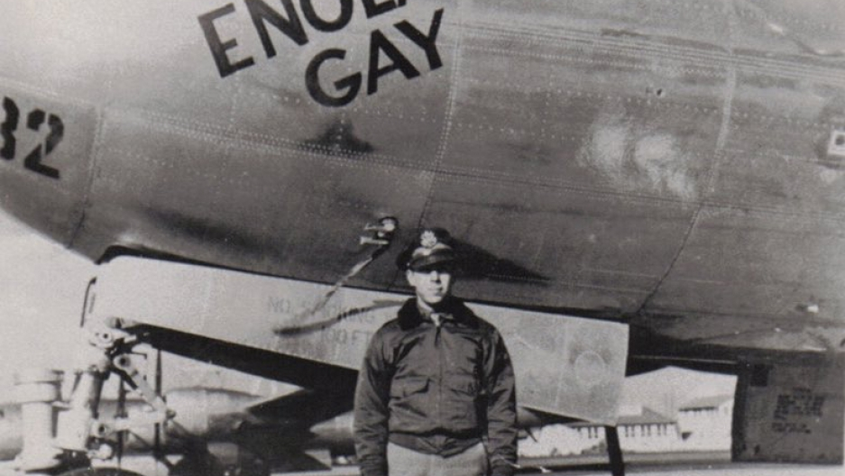 A uniformed man stands in front of the bomber Enola Gay