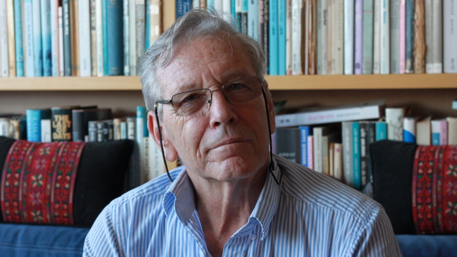 "Amos Oz in his Tel Aviv apartment. His bestselling memoir, ""A Tale of Love and Darkness,"" is on the bookshelf behind him, translated into more than two dozen languages."