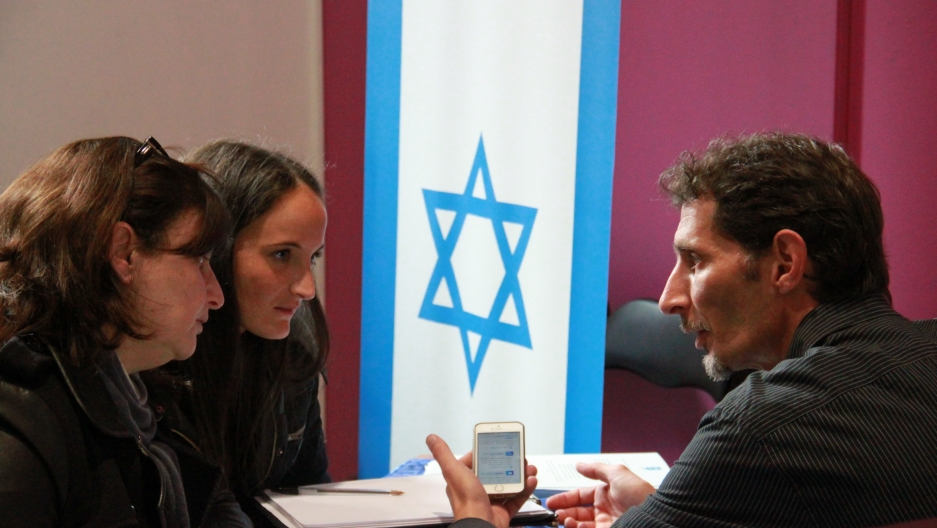 An Israeli government representative discusses Israeli immigration with prospective Jewish immigrants at an immigration expo in Paris.