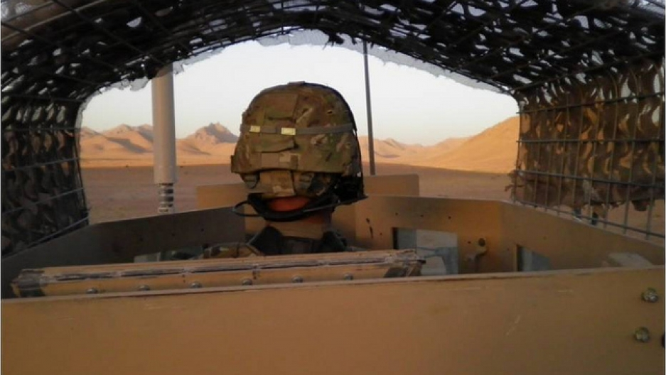 Spc. Jorge Villanueva, 2nd Battalion, 8th Field Artillery Regiment, 1st Stryker Brigade Combat Team, 25th Infantry Division, peers over the gunner's turret at Checkpoint 507 in the Daman District.