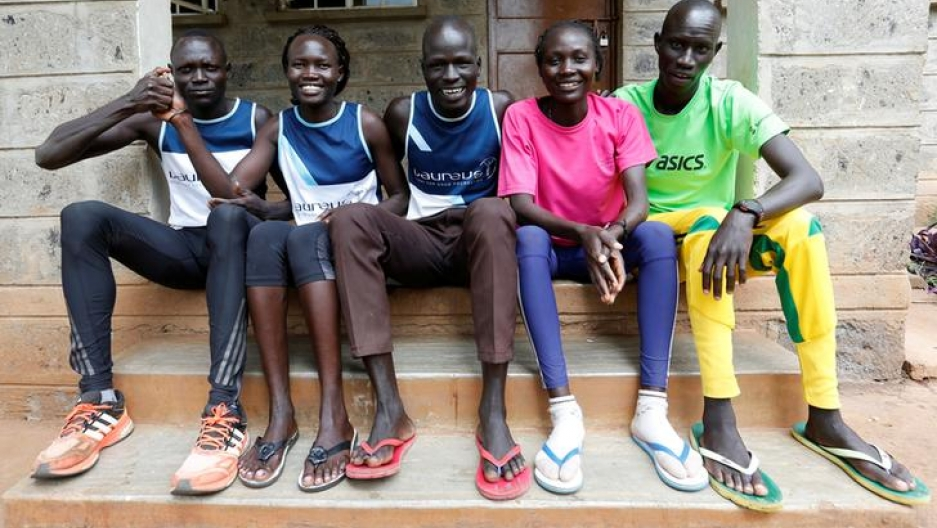 Five athletes from South Sudan who will be participating in the Summer 2016 Olympics sit beside each other on a short set of steps near their training grounds in Nairobi