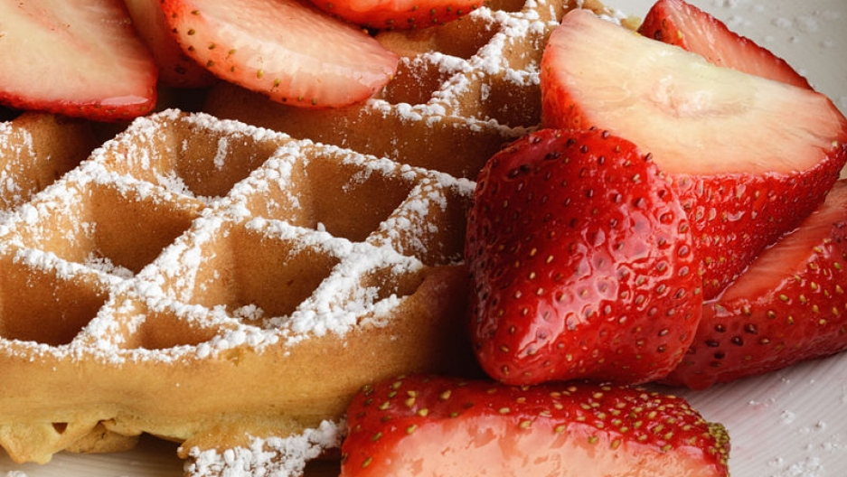 A Belgian waffle served traditionally with strawberries and confectioner's sugar.