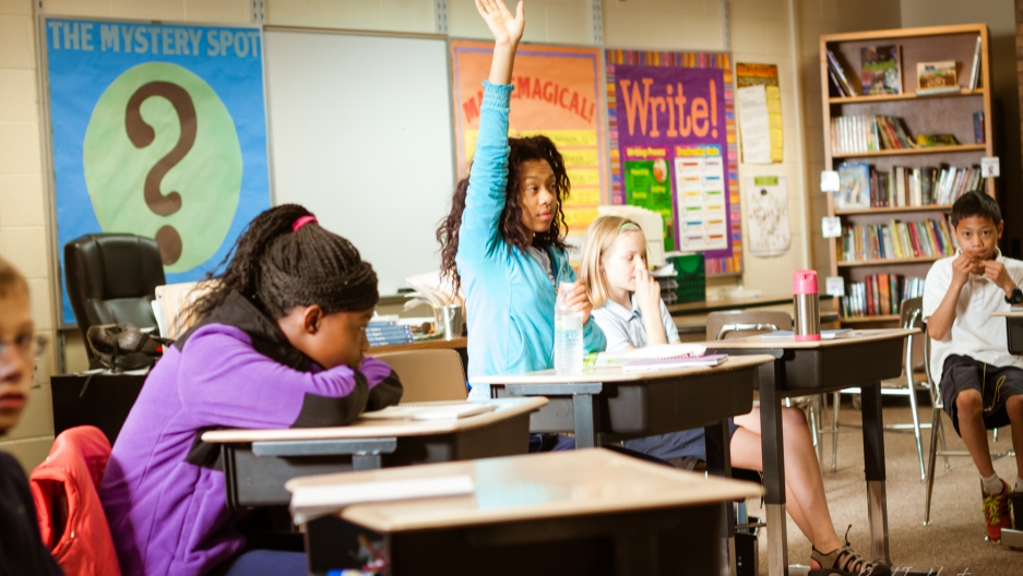 girl raised her hand in a classroom
