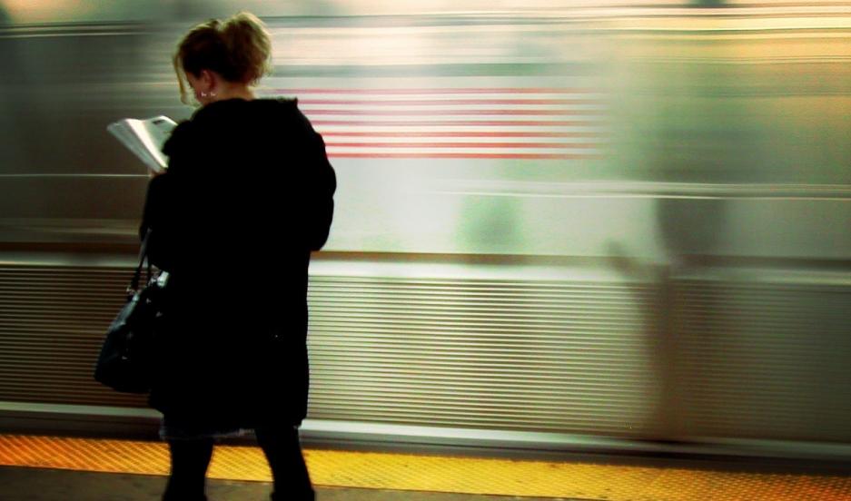 A woman reading on a New York City subway platform.