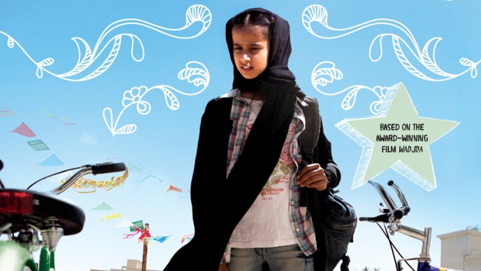 """Wadjda looks at her desire, a bicycle, on the book cover for Haifaa al-Mansour's the new young adult novel, """"The Green Bicycle."""""""