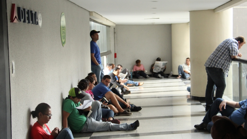 Dozens of desperate travelers wait in front of a Delta airlines ticket office at dawn in Caracas, Venezuela.