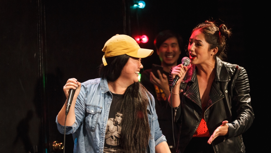 Two female performers are standing in front of each other holding microphones.