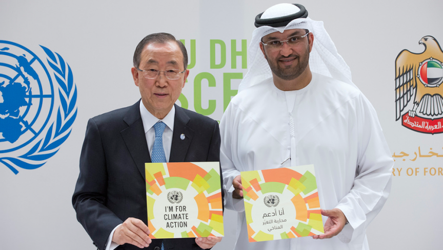 """UN Secretary-General Ban Ki-moon and Sultan Ahmed al-Jaber, climate change envoy of the United Arab Emirates, hold up signs that read, """"I'm for Climate Action"""", in English and Arabic, at a joint press conference in Abu Dhabi."""