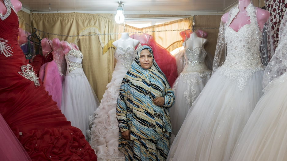 Um Mohammed, a Syrian refugee hailing from the southern Daraa region, stands in her wedding dress shop in Jordan's Zaatari camp. Expecting another child, Um Mohammed said she opened the shop a year and a half ago to help generate extra income for her grow