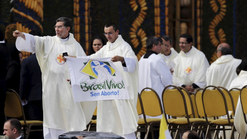 """A priest holds up a banner reading """"Brazil alive! Without abortion"""" while standing near an altar where Pope Francis later celebrated mass."""