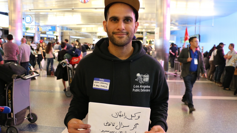 Man in sweatshirt with public defenders logo holds sign in Arabic