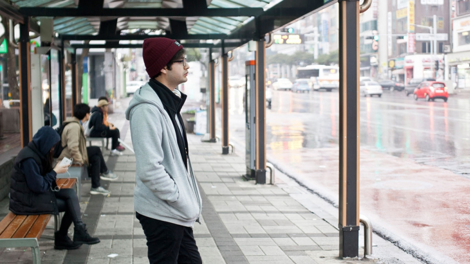 Ahmed Lababidi waits for the bus on Jeju Island. Lababidi left his war torn hometown, Aleppo,  fleeing across the Turkish border in 2012. He followed his younger brother to South Korea and settled on Jeju.