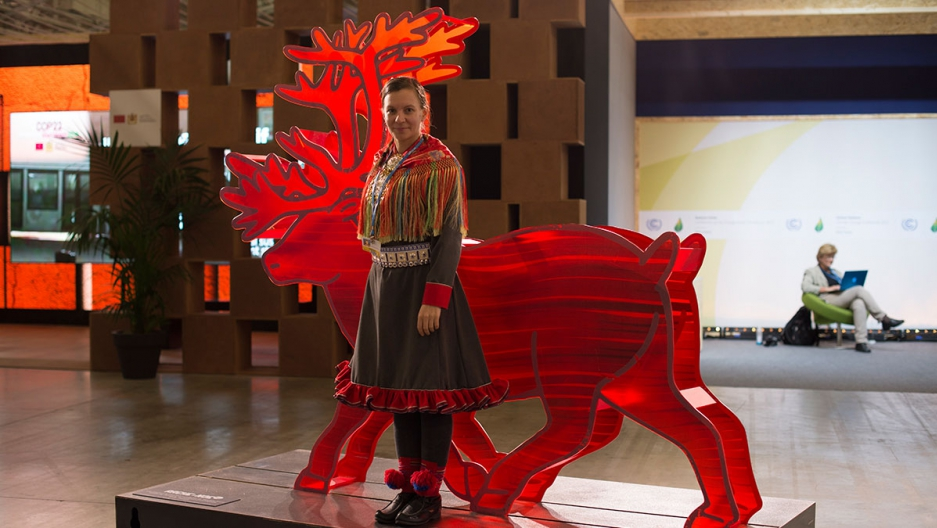 Aile Javo stands in front of a plastic reindeer at COP21.