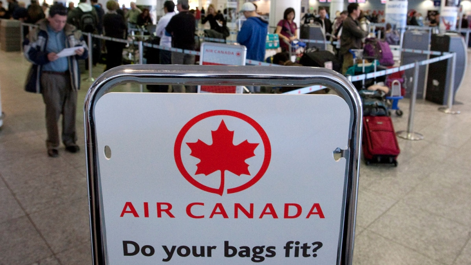 Air Canada travelers wait at the check-in area in Montreal.