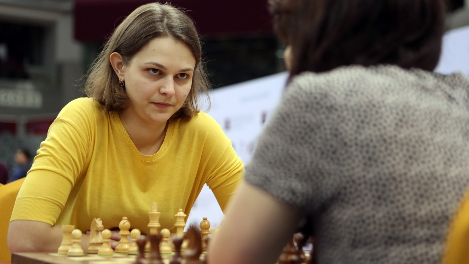 Ukraine's grandmaster Anna Muzychuk, wearing a yellow shirt, stares down her opponent across a chess board.