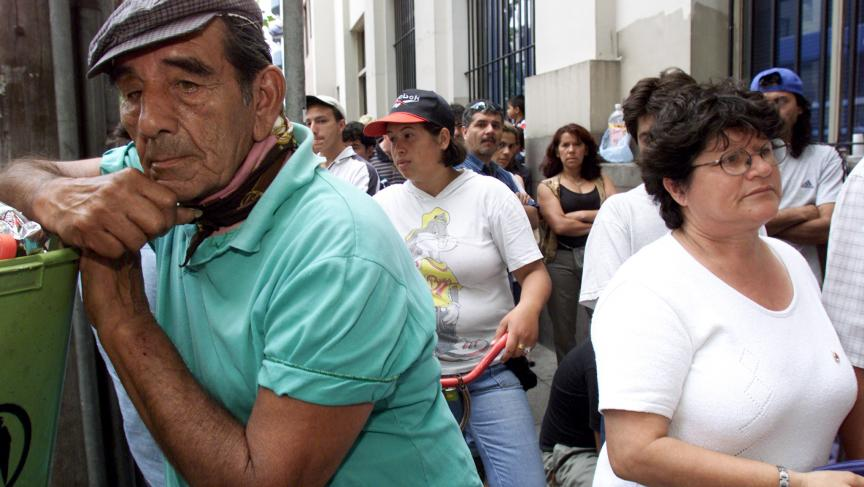 Unemployed Argentines and workers line up outside the Banco de la Nacion in Buenos Aires trying to collect their money, December 21, 2001. Argentina would default on its sovereign debt days later.