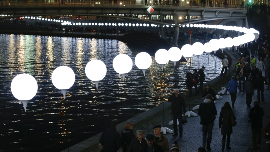 "People walk under the ""Lichtgrenze"" installation along the River Spree in Berlin on November 8, 2014. A part of the inner city of Berlin was temporarily divided with a light installation to commemorate the 25th anniversary of the fall of the Berlin Wall."