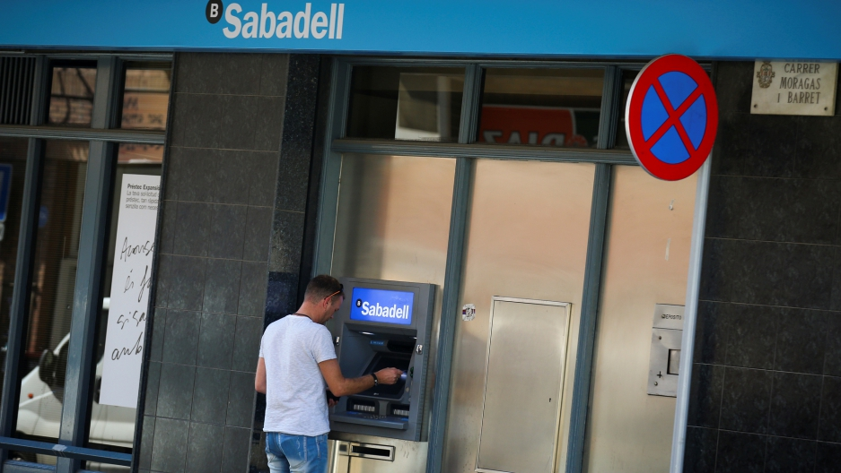 A man uses a cashpoint at a Sabadell bank branch in Pineda de Mar, north of Barcelona.